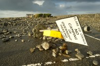 A sign ripped from the ground in the debris-covered car park at Doolin pier following the storm. Photograph by John Kelly.