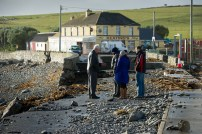 People stand on the rubble-strewn road in Kilbaha, which is covered by rocks and undermined in places following the latest high seas and gales. Photograph by John Kelly.