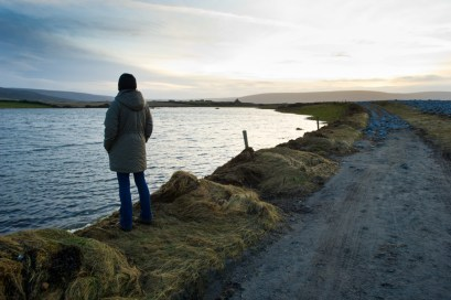 A woman looks over a flooded area at The Flaggy Shore caused by the latest high seas and gales. Photograph by John Kelly.