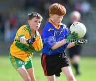 Liam Griffin of Carrigaholt/Moveen in action against Darragh Cassidy of Carron/New Quay,Ballyvaughan/Fanore during their Primary Schools Div 3 Football 11-Aside final at Kilrush. Photograph by John Kelly