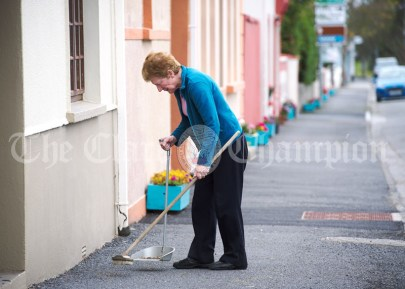 A local brushes up the footpath outside her premised, ahead of the visit of the United States President Donald J. Trump to Doonbeg. Photograph by John Kelly