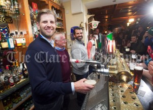 Eric and Don Junior Trump take on barman duties under the tutorship of Publican Tommy Comerford in his bar during their walkabout in Doonbeg Village. Photograph by John Kelly