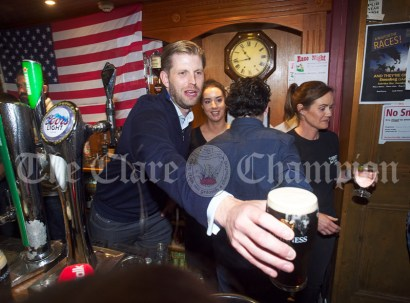 Eric Trump take on barman duties and hands out drinks to thirsty customers in Tubridy's Bar during their walkabout in Doonbeg Village. Photograph by John Kelly