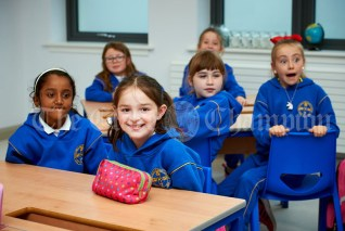 Pupils watch out for their friends arriving to class during the first day of school at the newly built Ennis CBS primary school. Photograph by John Kelly