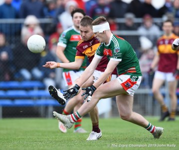 Seanie Malone of Miltown accidentally scoring a point against his ovn team despite Dermot Coughlan of Kilmurry Ibrickane during their senior football county final at Cusack Park. Photograph by John Kelly.