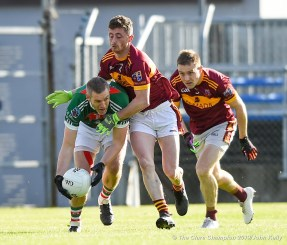 Enda Couglan of Kilmurry Ibrickane in action against Eoin O Brien and Seanie Malone of Miltown during their senior football county final replay at Cusack Park. Photograph by John Kelly.
