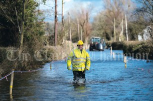 Tom Lynch from Bridgetown, an employee of Clare County Council, wades between houses in Springfield making sure the water pumps continue to function, behind him a local farmer moved silage balles to higher ground. Photograph by Eugene McCafferty on 24/02/2020