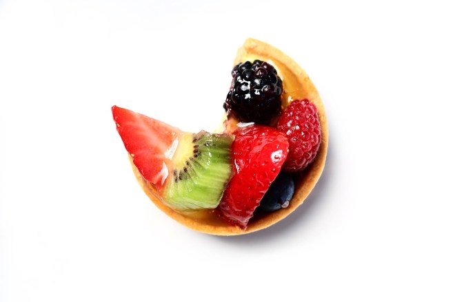 Overhead shot of fruit tartlet with strawberry slices, kiwi slice, blueberry, and blackberry with a quarter of the tartlet missing