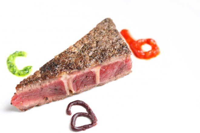 Triangular prism bison steak with a). wine reduction sauce next to the edge that looks like the base of the triangular prism b). red pepper salsa next to the edge on the right side of the triangular steak c). green chimichurri sauce next to the edge that looks as though it is the hypotenuse of the triangular steak