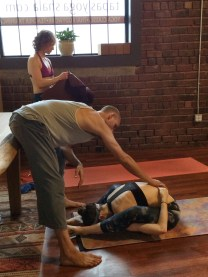 Tim giving me a Supta Kurmasana adjustment in my Primary Series practice.