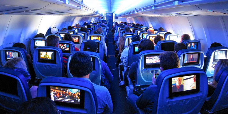 Passengers flying coach on a commercial flight with built in tv screens
