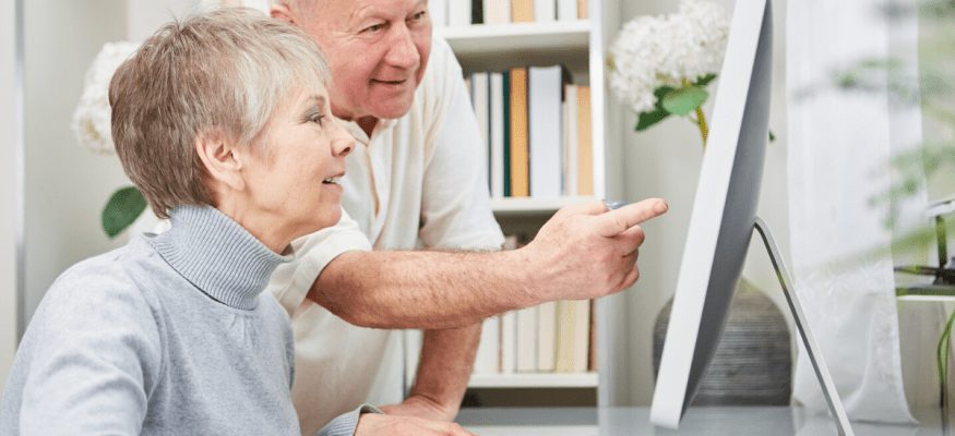 Senior citizen couple looking deals and savings on a computer
