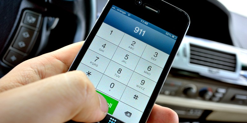 Calling to 911 for help from a digital smartphone new device. Holding a black Iphone 4S in the left hand inside the car.
