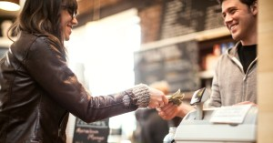 Woman paying cashier with a debit card