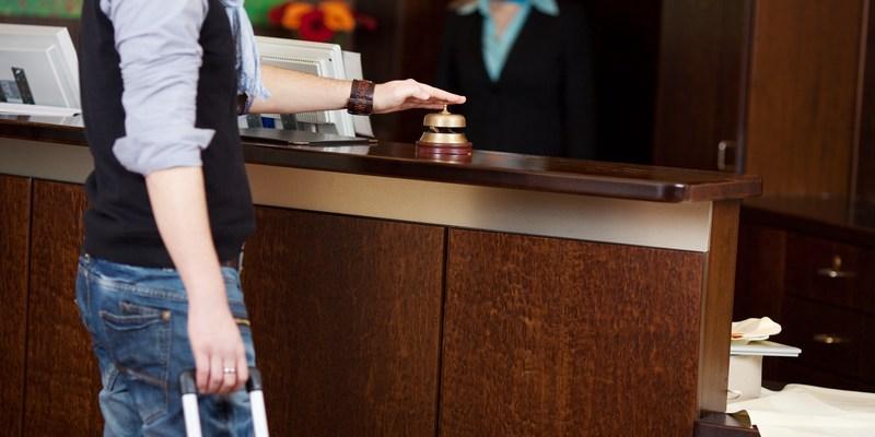Customer ringing bell at hotel front desk