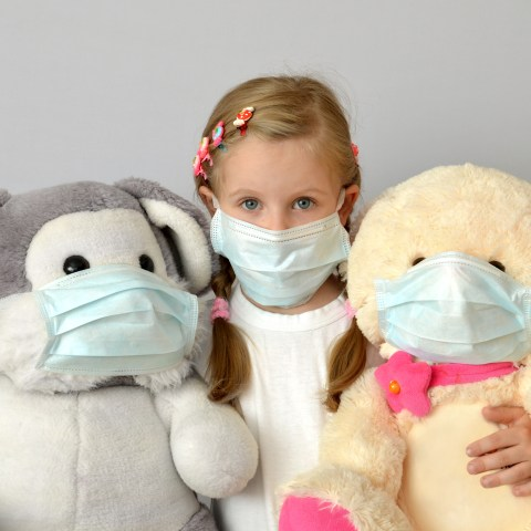 Girl child with surgical masks on stuffed animals and bears