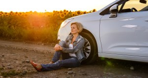 woman on side of road new broken down car