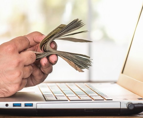 man holding money at computer