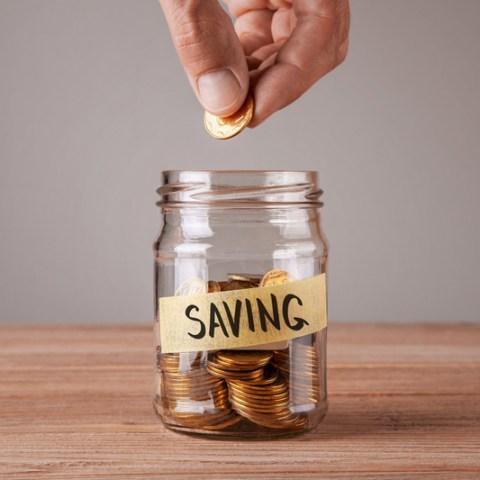 man saving coins in a jar