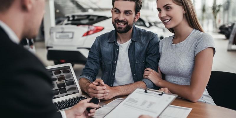 happy couple at car dealership