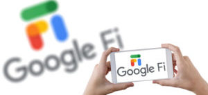 Holding a smartphone with Google Fi service and a large Google Fi logo blurred in the background