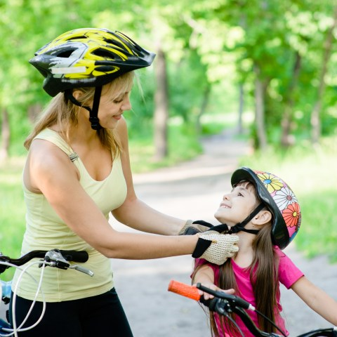 mother with child on bicycle adjusting helmet