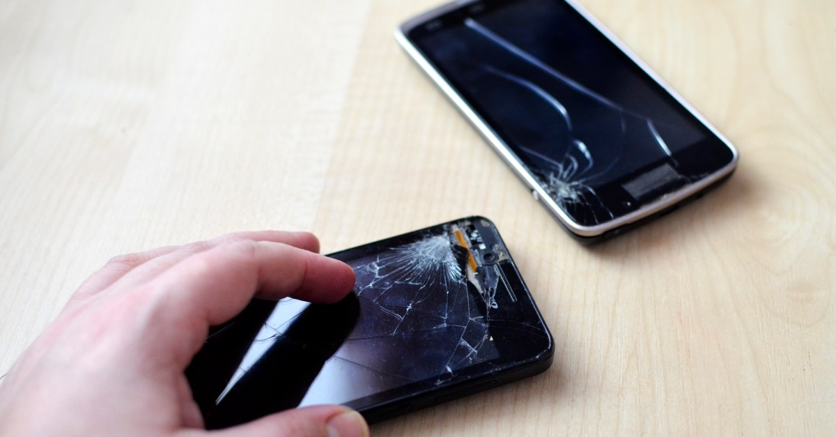 man holding cell phone with cracked screen