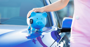 Woman with piggy bank on the hood of a new car