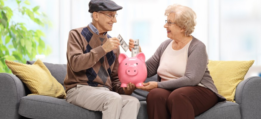 Seniors sitting on a sofa and putting money into a piggybank