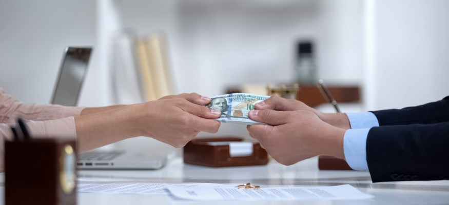Male and female hands pulling money, dividing marital property during divorce.