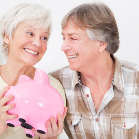 senior couple saving money with a piggy bank