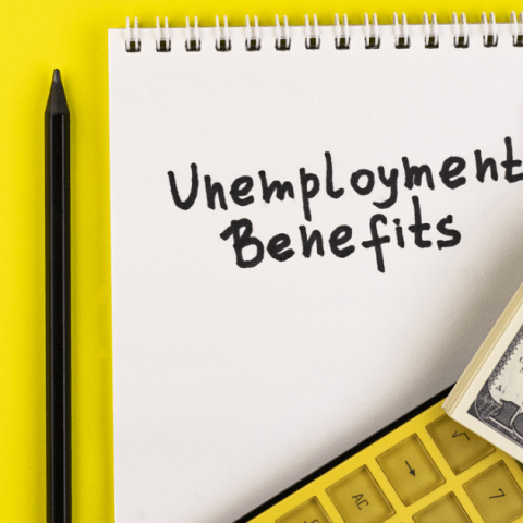 unemployment benefits written on pad surrounded by money and calculator