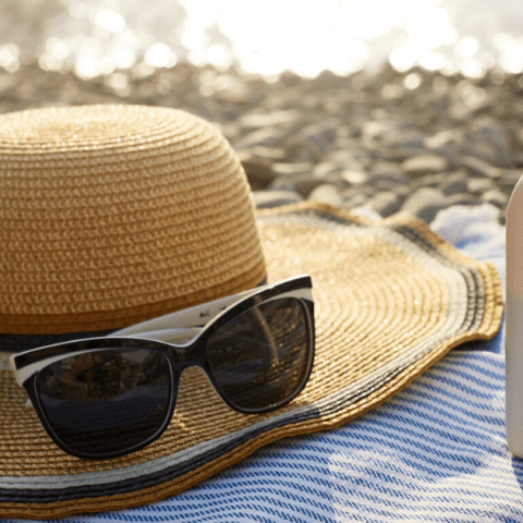 Suntan cream bottle and sunglasses on beach towel with sea shore on background. Sunscreen on deck chair outdoors on. Shell, plastic.