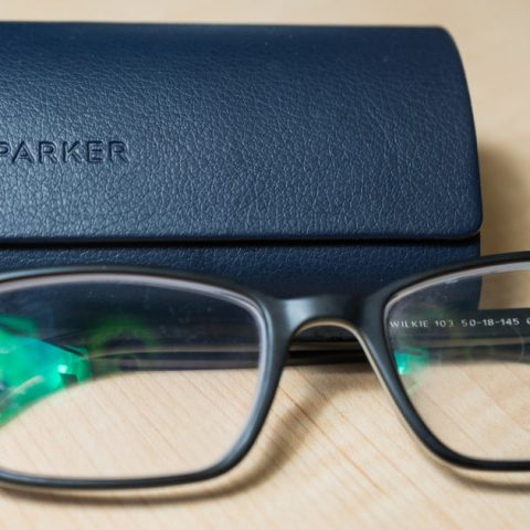A pair of Warby Parker glasses and a case sitting on a table