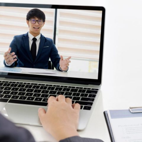 A potential employee on his laptop in an online video interview.