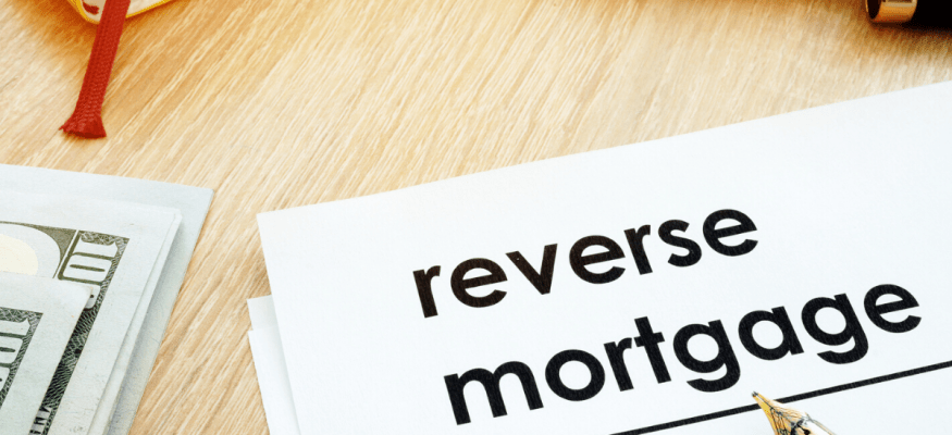 reverse mortgage documents on a desk surrounded by $100 bills and a calculator