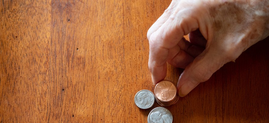 Woman counting loose change due to coin shortage