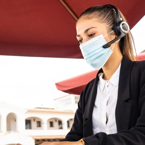 woman working remote job in mask on beach