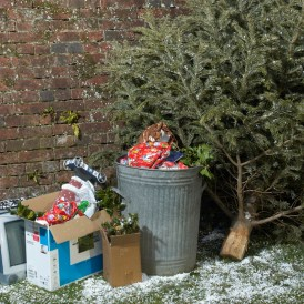 Garbage after Christmas piled up against brick wall with Christmas Tree