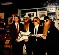 "ZZ Top donates the custom ""Muddywood"" guitar to Sid Graves at the Carnegie Public Library."