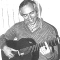 classical guitarist john williams holding guitar