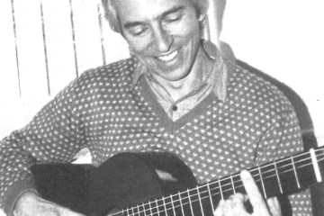 classical guitarist john williams holding guitar