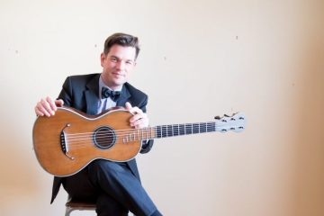 classical guitarist pascal valois sits in a chair with his guitar