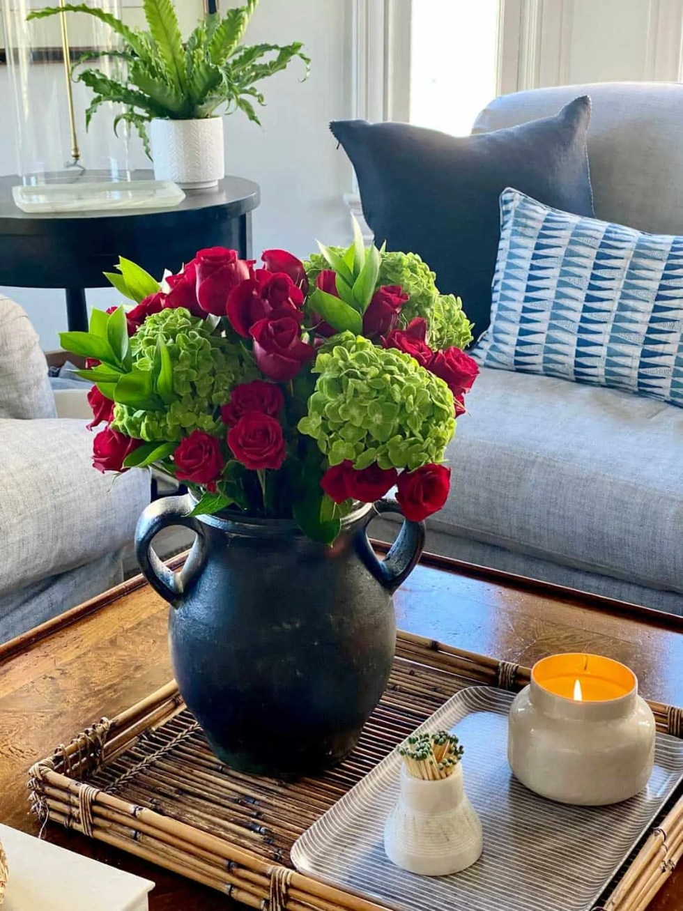 Red roses and green hydrangea flower arrangement on coffee table