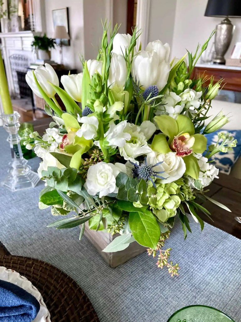 White flower centerpiece with green orchids