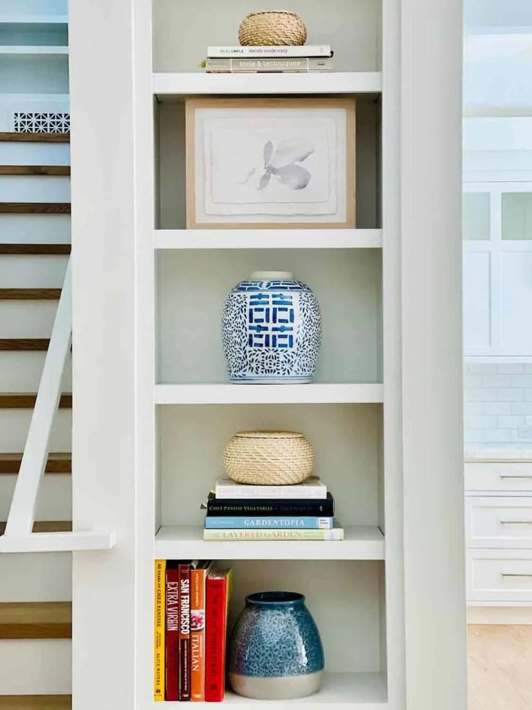 Cookbooks and blue vases on kitchen bookshelves
