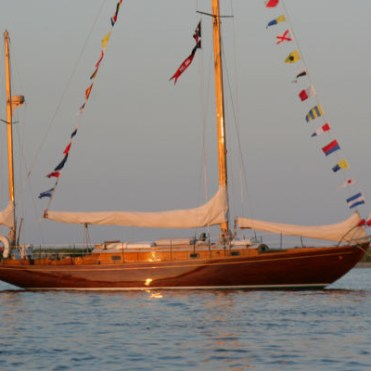 Concordia yawl dressed overall at anchor during the sunset