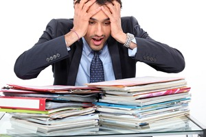 Photo of a panicked person surrounded by paperwork. MarkBook software could help out
