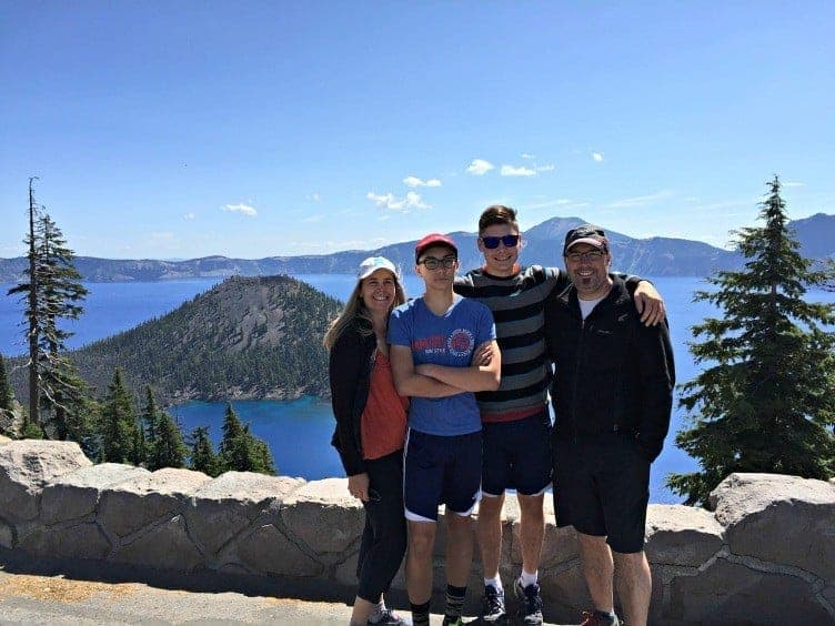family of four posting at crater lake showing that family travel matters