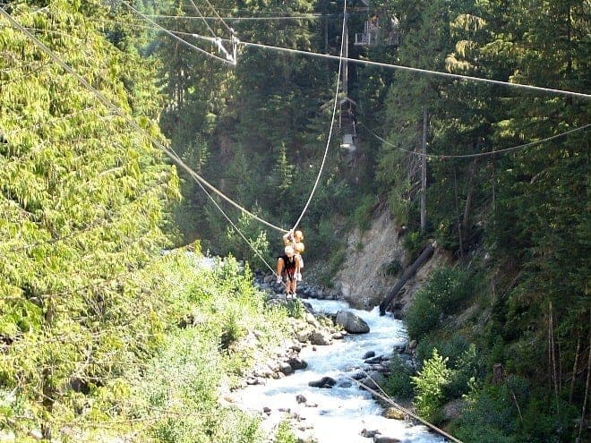 two people zip lining over Fitzsimmons Creek in Whistler in summer
